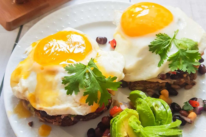 Täysjyväleipää, kananmunia, avokadoa ja papusalsaa